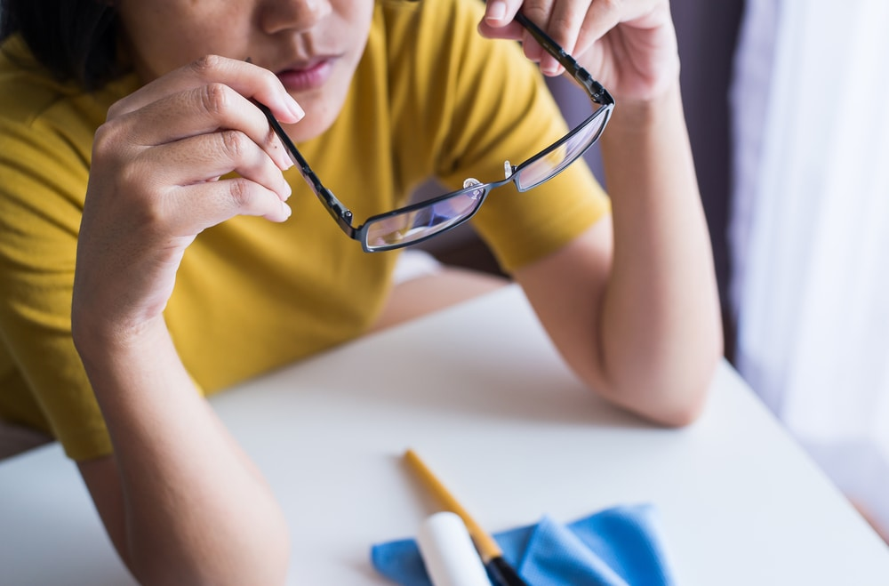 A girl cleaning her glasses with lens cleaners