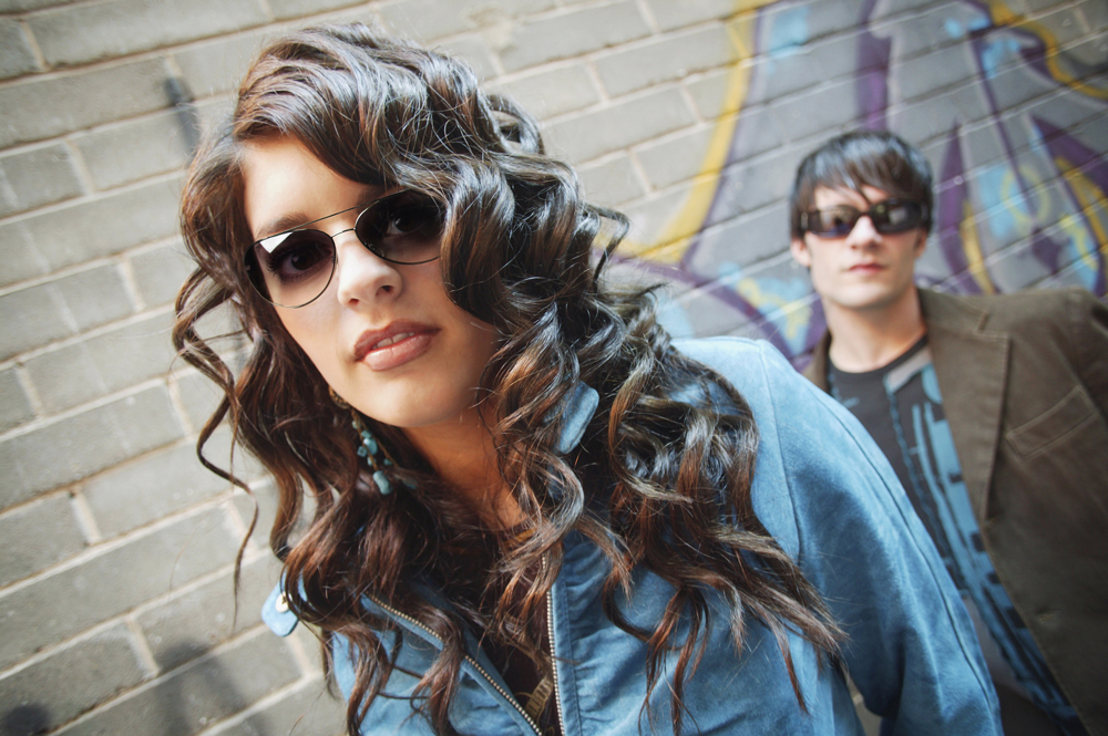 Young girl wearing designer eyewear with a boy in background